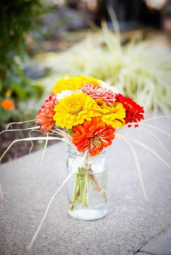 Decoração com potes de vidro e arranjos de flores