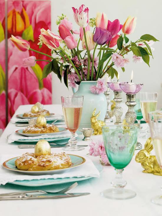Decoração de Páscoa com ovos coloridos e arranjos de flores na mesa